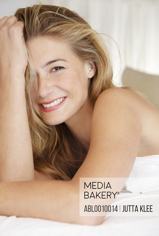 Woman Lying on Bed Smiling