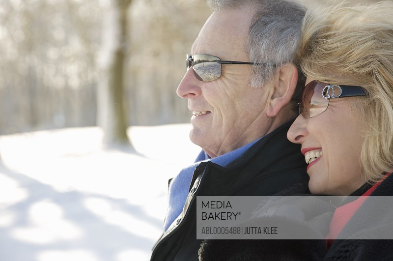 Profile of a smiling mature couple standing in the snow - close up
