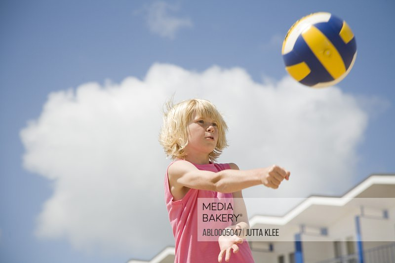 Blonde boy playing volleyball