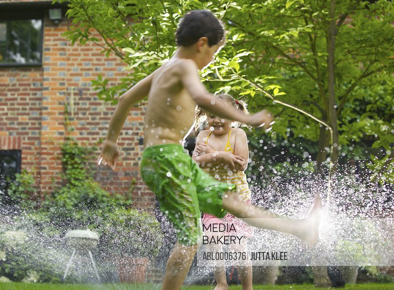 Boy and Girl Playing with Sprinkler