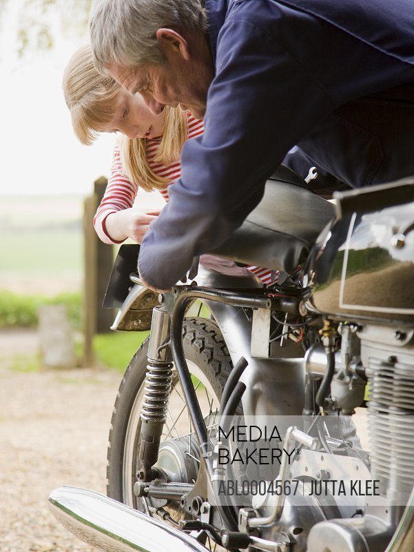 Young girl helping grandfather repairing motorbike