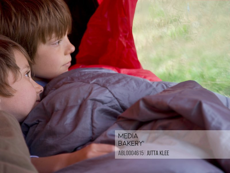 Portrait of two boys sitting in a tent looking out
