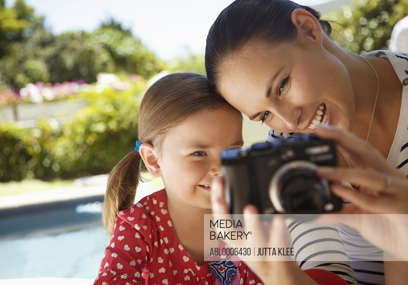 Woman and Young Girl Looking at Digital Camera