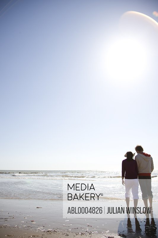 Back of young couple walking on a beach
