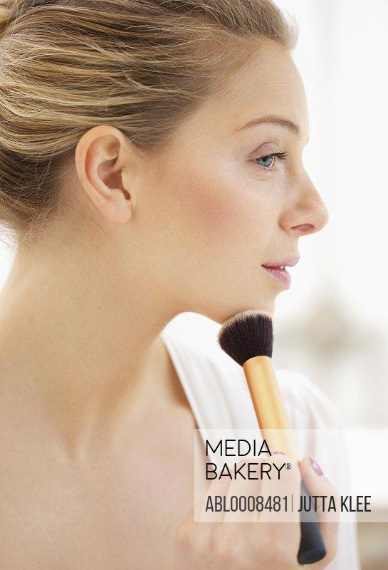 Woman Applying Blusher on Chin