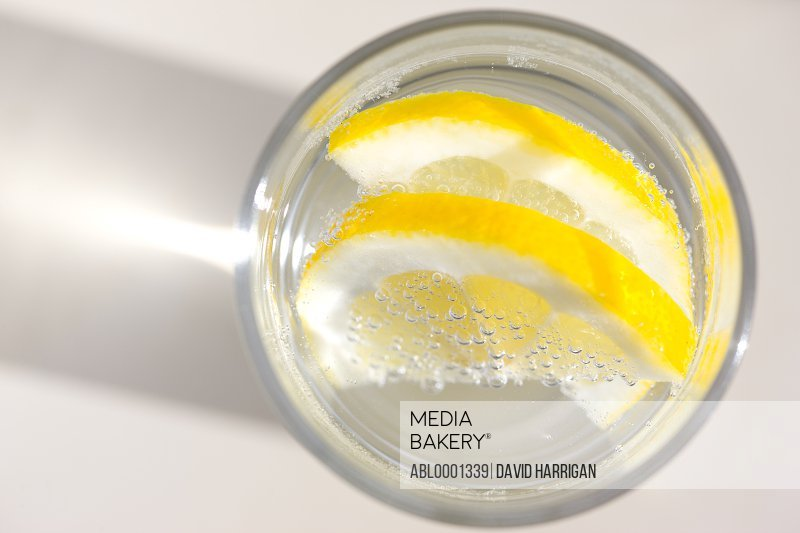 Extreme close up of a glass of sparkling water with sliced lemon - high angle