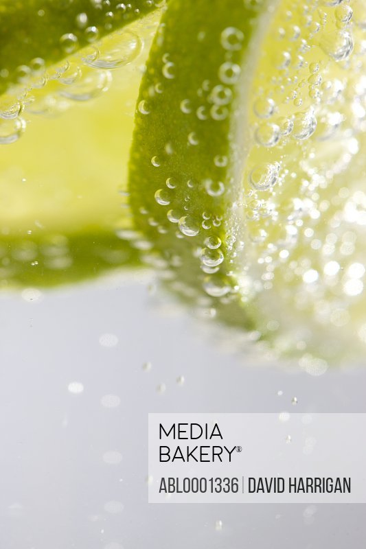 Extreme close up of slices of lime floating in sparkling water