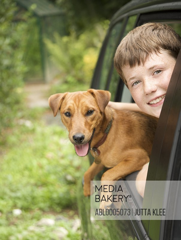 Young boy  and his dog leaning out of car window