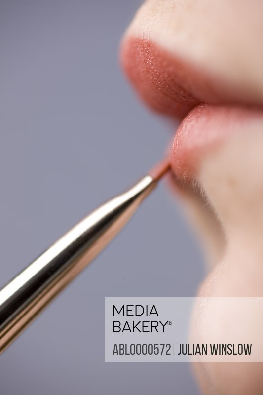 Close up of young woman lips with lipstick brush