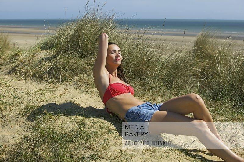 Woman Sunbathing on Sand Dune by Ocean