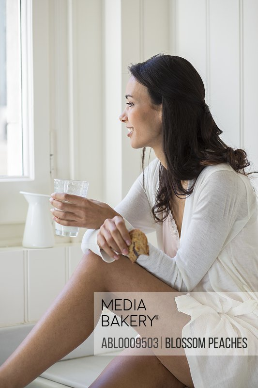 Woman Sitting Having Milk and Cookie