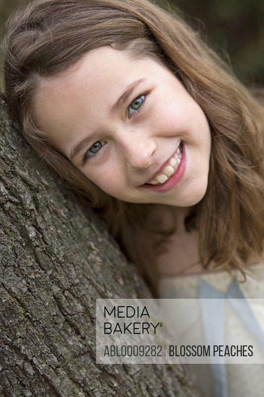 Smiling Young Girl Leaning on Tree Trunk, Close-up View