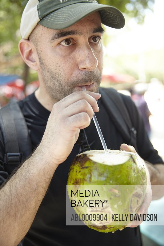 Man Drinking from Coconut