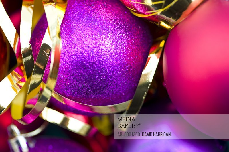 Extreme close up of red and purple Christmas baubles and a gold ribbon