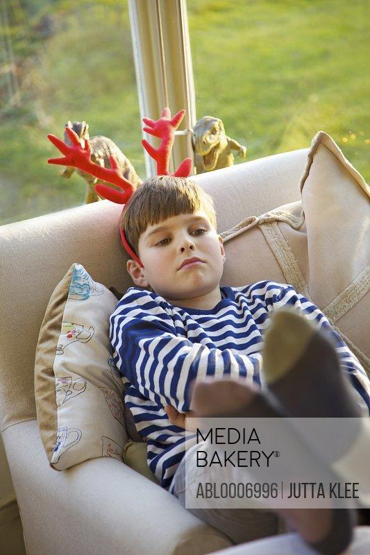 Sulking Boy Wearing Christmas Antlers