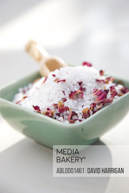 Close up of a ceramic bowl filled with bath salts and petals