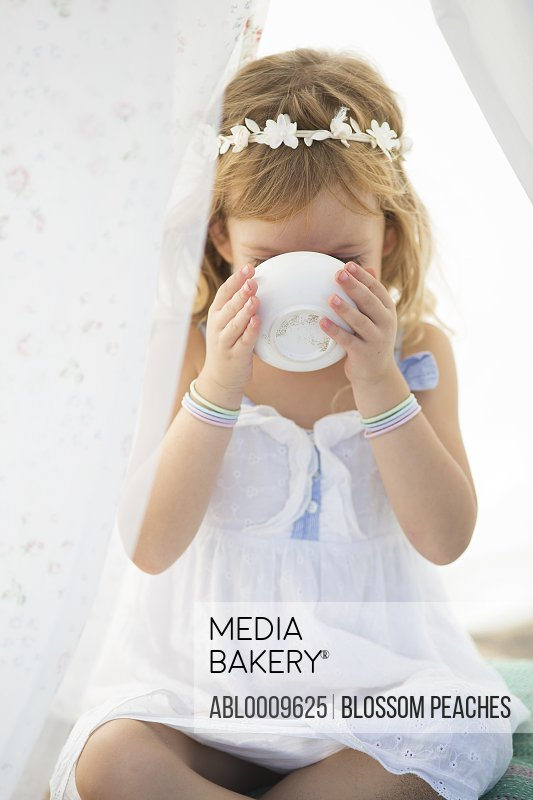 Young Girl under Tent Drinking from Cup