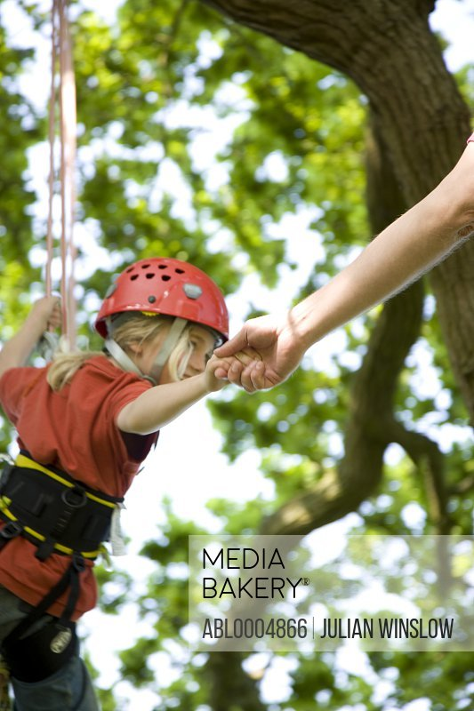 Young girl hanging from tree holding onto rope and  man hand