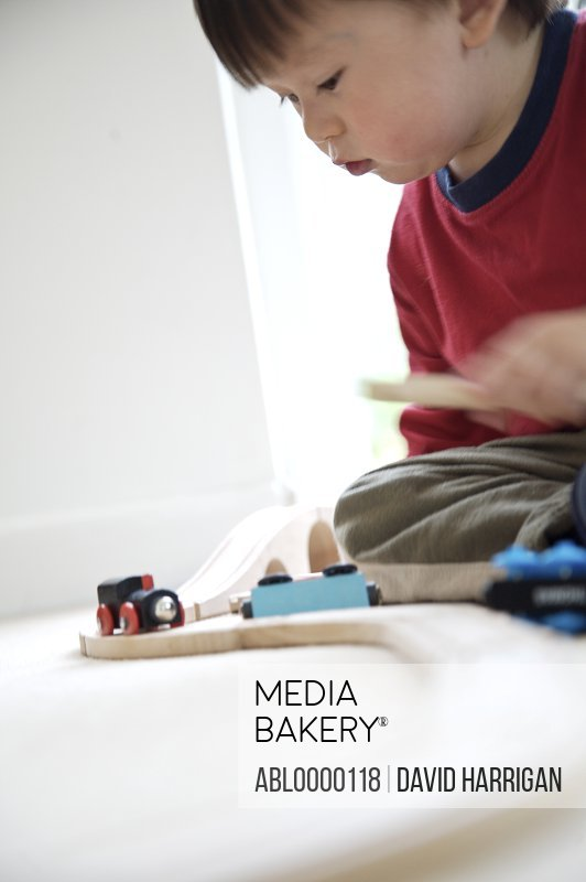 Young boy playing with wooden train set