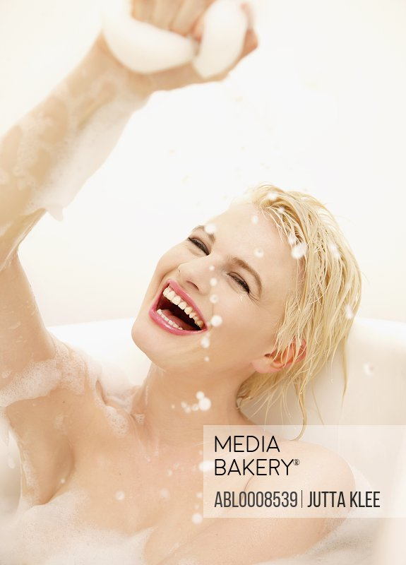 Smiling Young Woman Having a Bath Playing with Foam