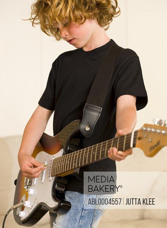 Young boy playing electric guitar