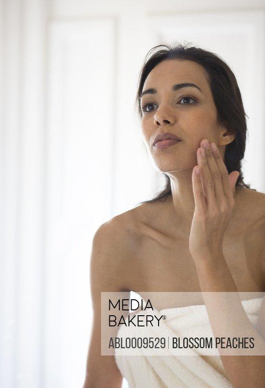 Woman Applying Moisturizer on Face