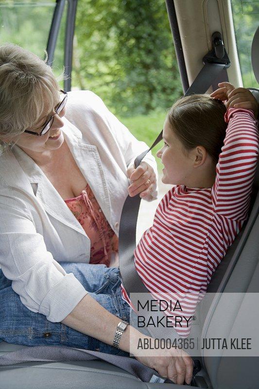 Grandmother adjusting seatbelt for granddaughter