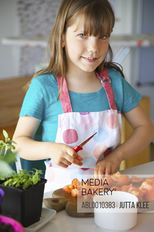 Smiling Young Girl Cutting Tomatoes