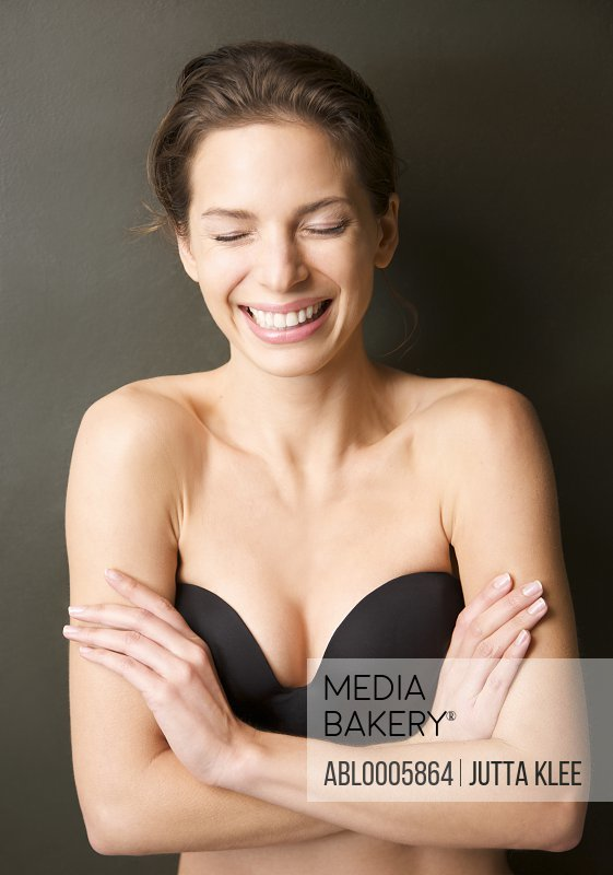 Smiling young woman wearing a strapless black bra