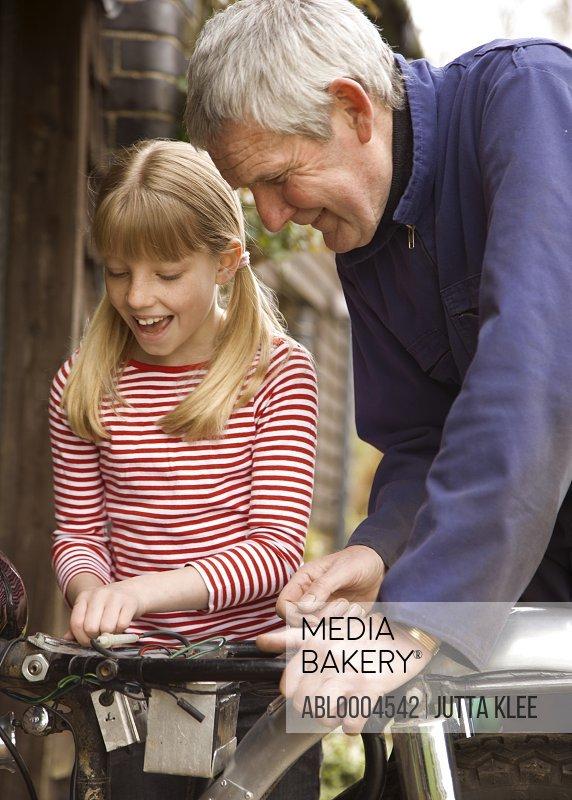 Young girl helping grandfather repairing motorbike