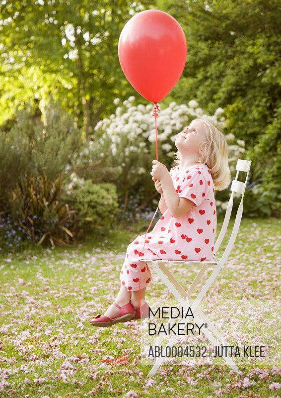 Young girl sitting on a chair in the garden holding a red balloon