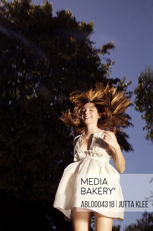 Laughing young woman leaping mid air from trampoline