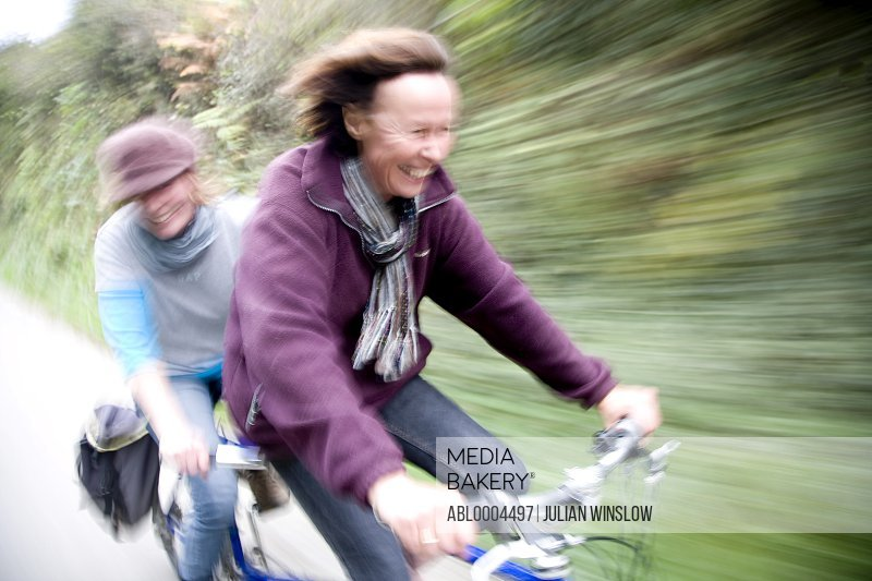 Two women on a tandem bicycle smiling