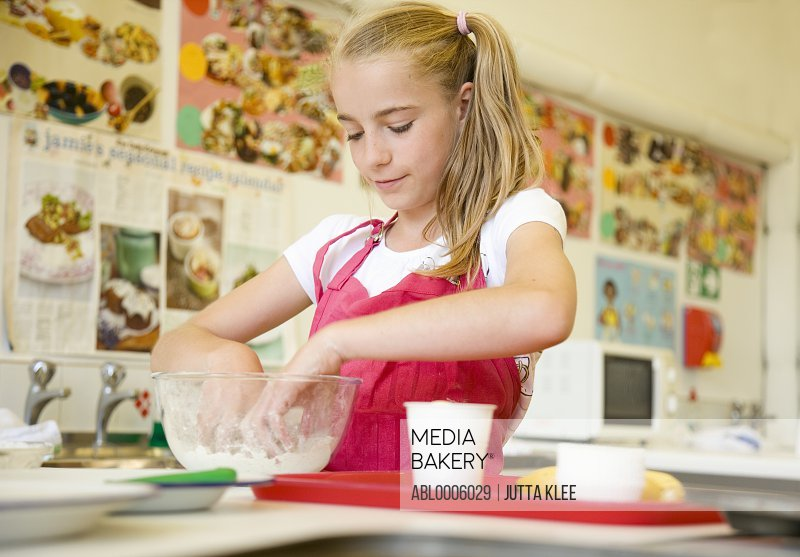 Young girl in cookery class kneading