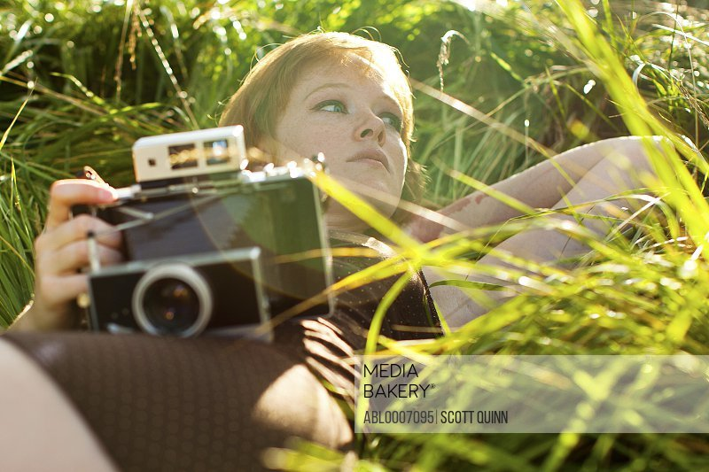 Woman Lying on Grass Holding Vintage Camera