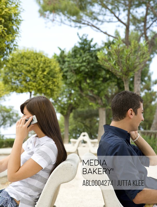 Young couple sitting back to back talking on cell phone