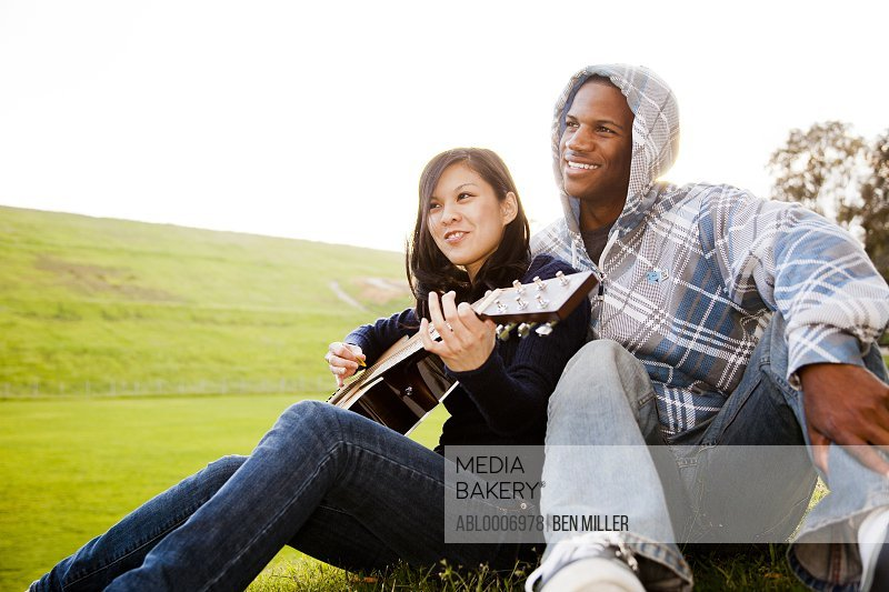Young Couple with Woman Playing Guitar