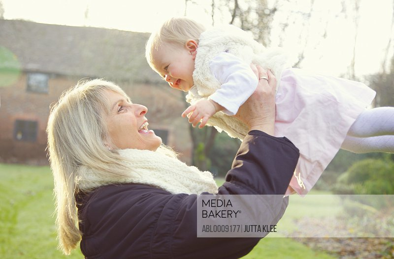 Mother Lifting Baby Daughter Outdoors