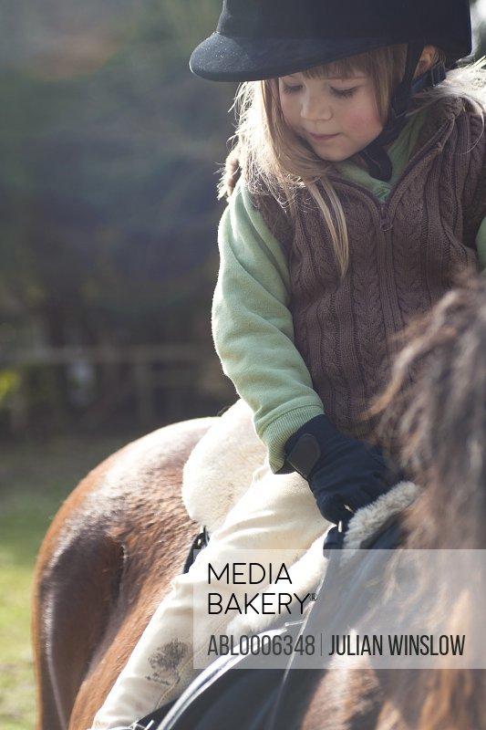 Young girl riding a horse