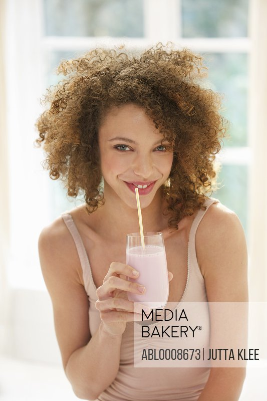 Young Woman Drinking Smoothie with Straw