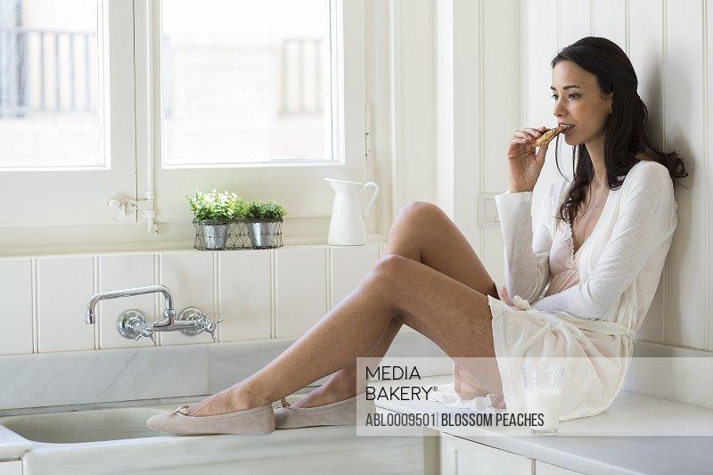 Woman Sitting on Kitchen Worktop Eating Cookie