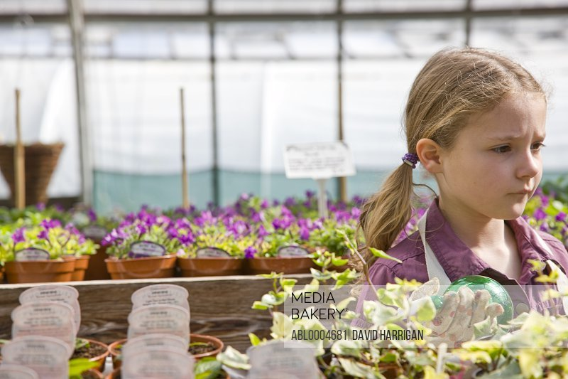 Portrait of a girl amongst flowerpots inside greenhouse