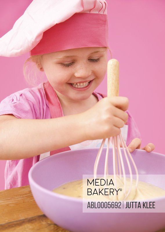 Smiling young girl whisking cake mix
