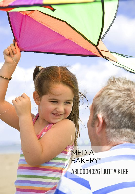 Young girl holding kite and smiling to her father