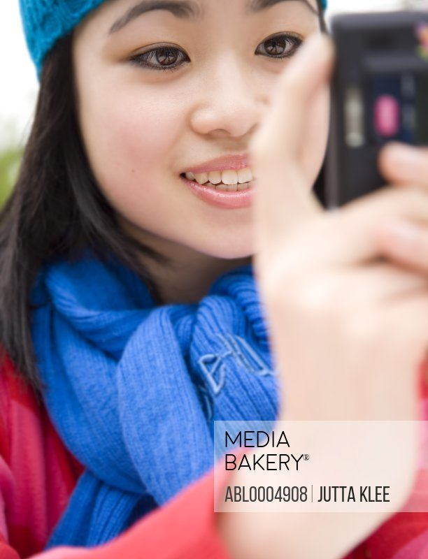 Close up of smiling teenaged girl taking a self-portrait with camera