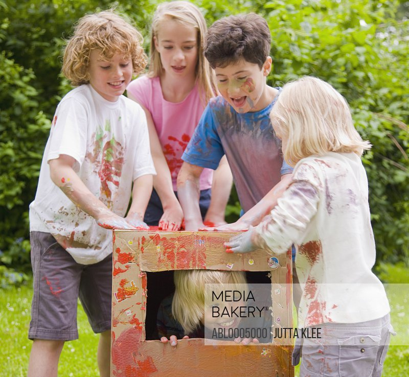 Children covered in watercolor paint playing in a garden, one of them is in a cardboard box