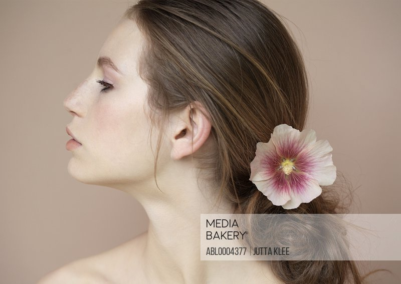 Profile of beautiful young woman with flower holding hair back