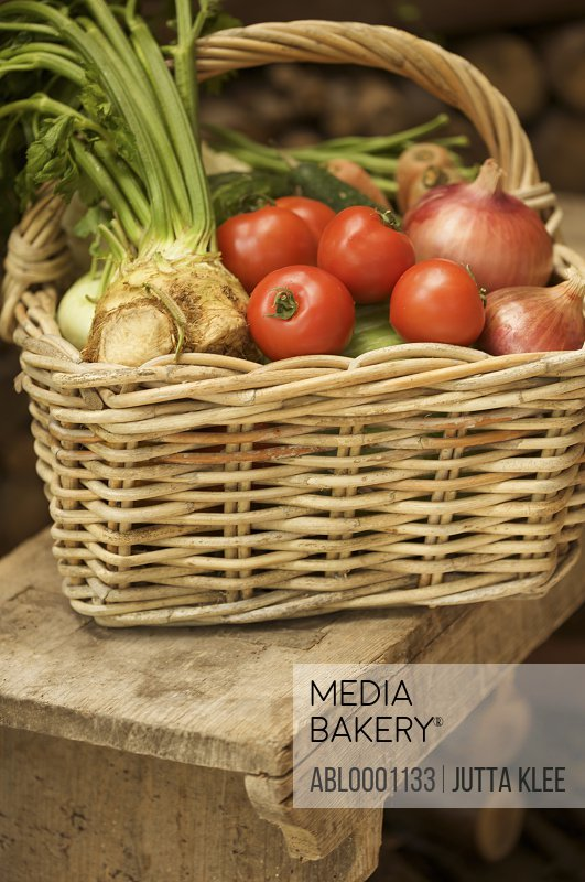 Close up of wicker basket filled with mixed vegetables on a wooden bench