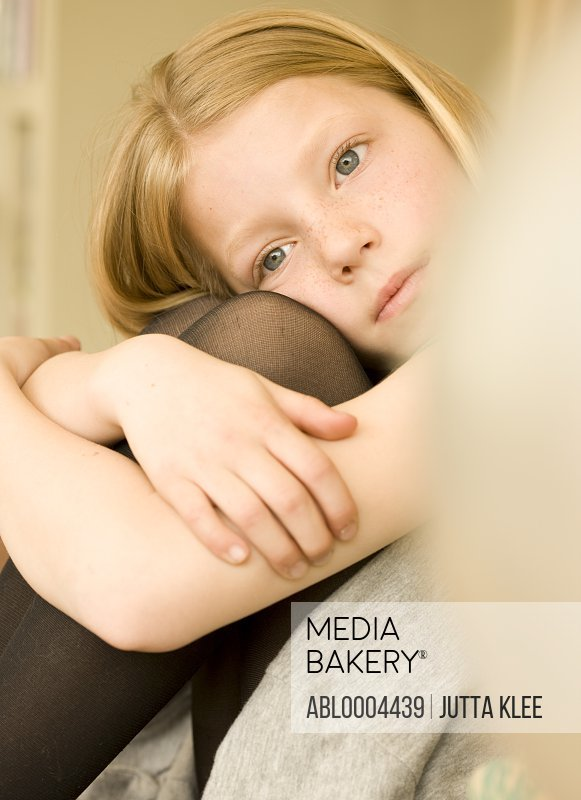 Girl with head resting on knee