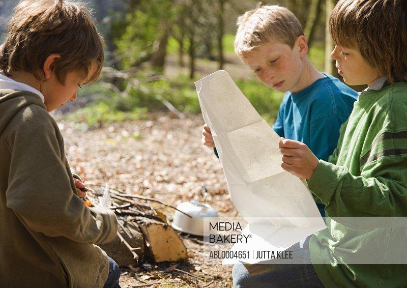 Three boys kneeling around campfire looking at map